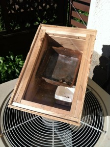 The solar wax melter. The wax melts in the pan and filters through a metal screen into a paper carton.