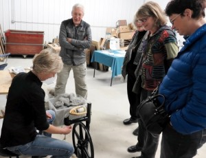 Tara Smith of Green Tara Farm demonstrates a spinning wheel during the 2015 Fosston Fiber Festival. Photo by Alethea Kenney.