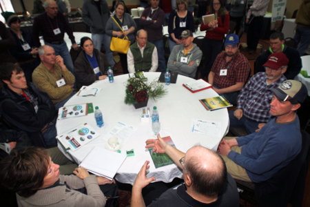 MSHS attendees crowd the Gabe Brown Discussion Table at the 2014 event. Each presenter at the Summit held a successive gathering at the Discussion Tables, allowing for more intimate conversation as well as farmer networking.