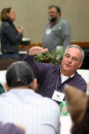 Midwest Soil Health Summit presenter and soil health pioneer Rick Bieber chats with attendees at the MSHS Discussion Tables.